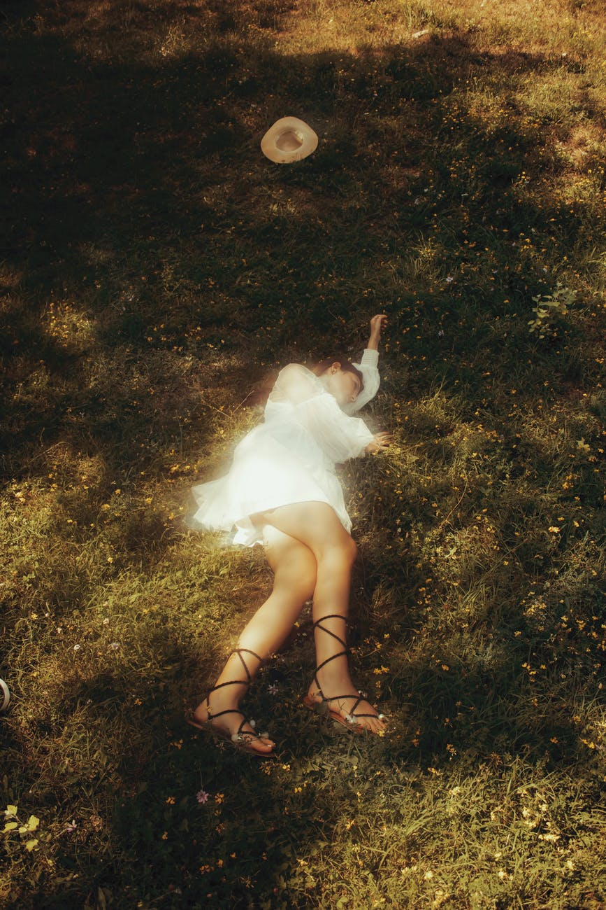 unrecognizable stylish woman sleeping on meadow in summer