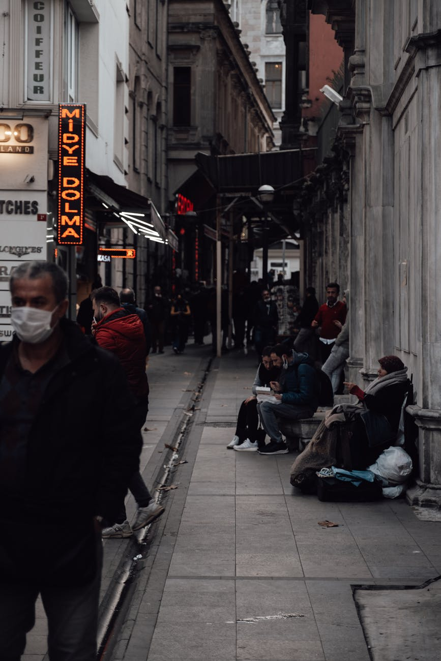 homeless woman with belongings on crowded street