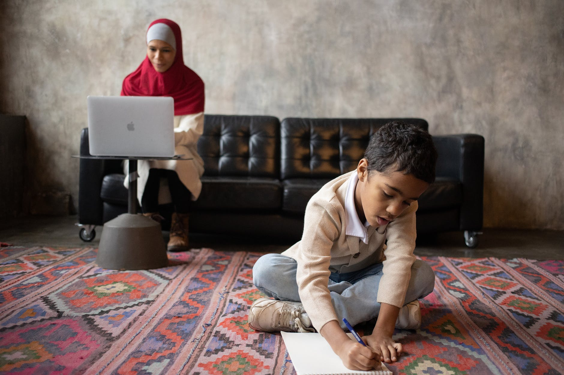 arabian mother in hijab working with laptop while son writing