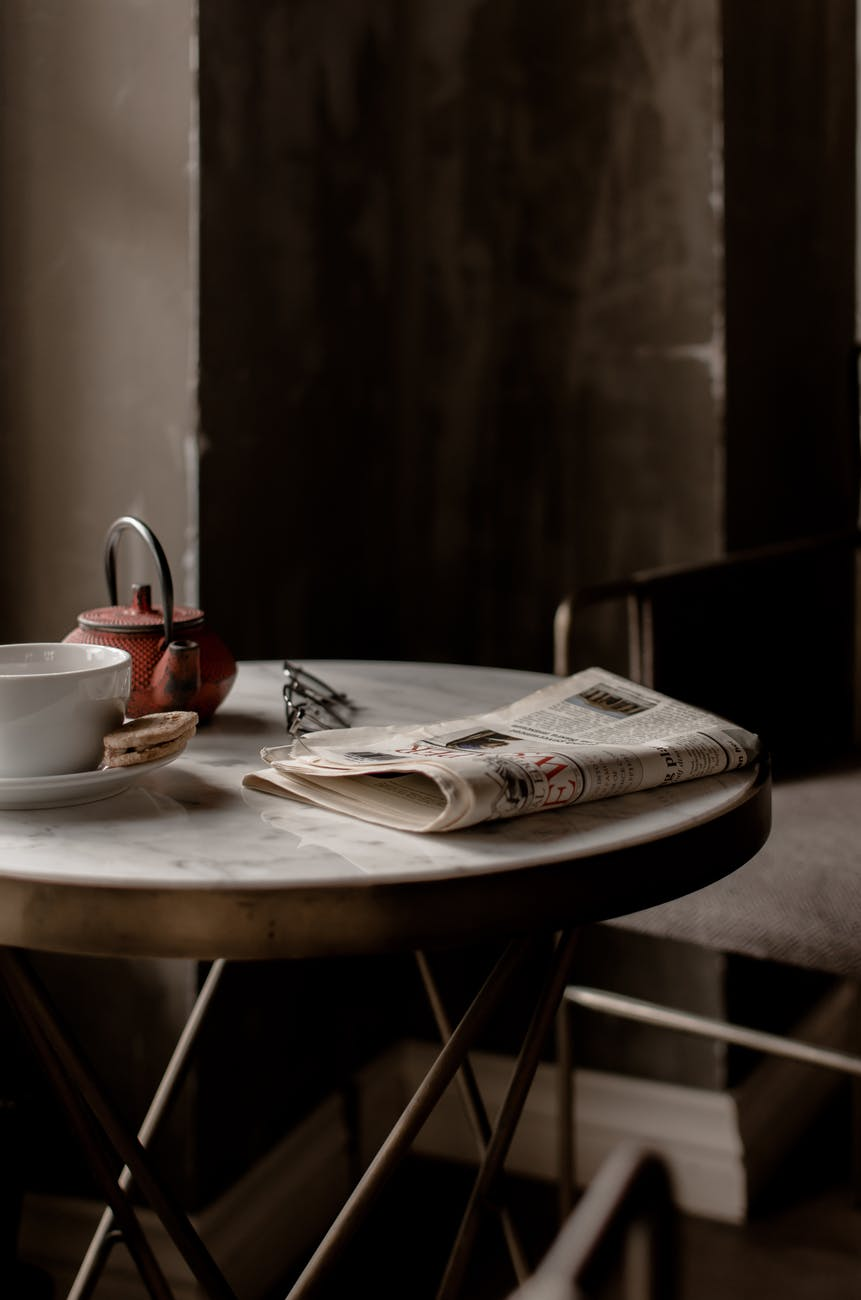tea set and newspaper placed on round table near comfortable chair