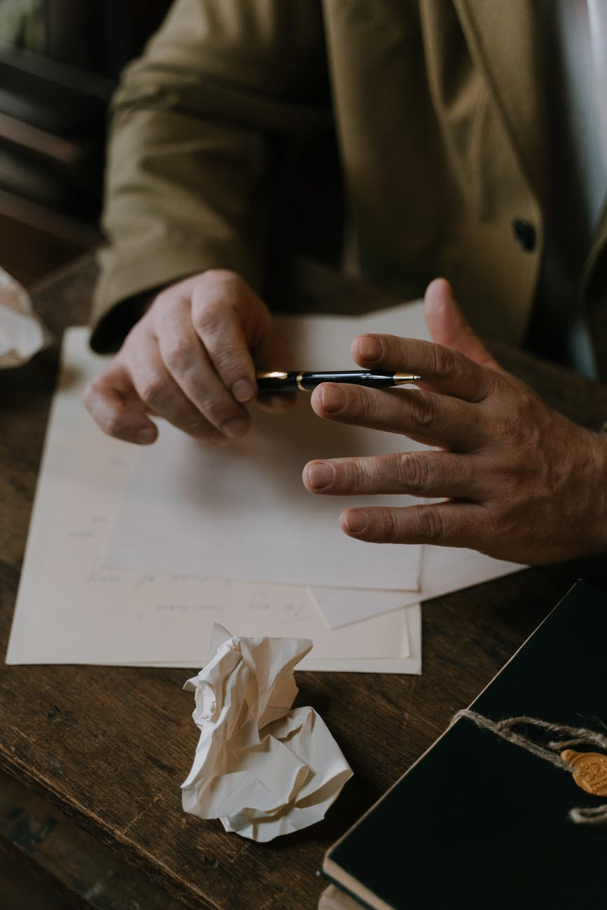 crop author with pen and paper working at table