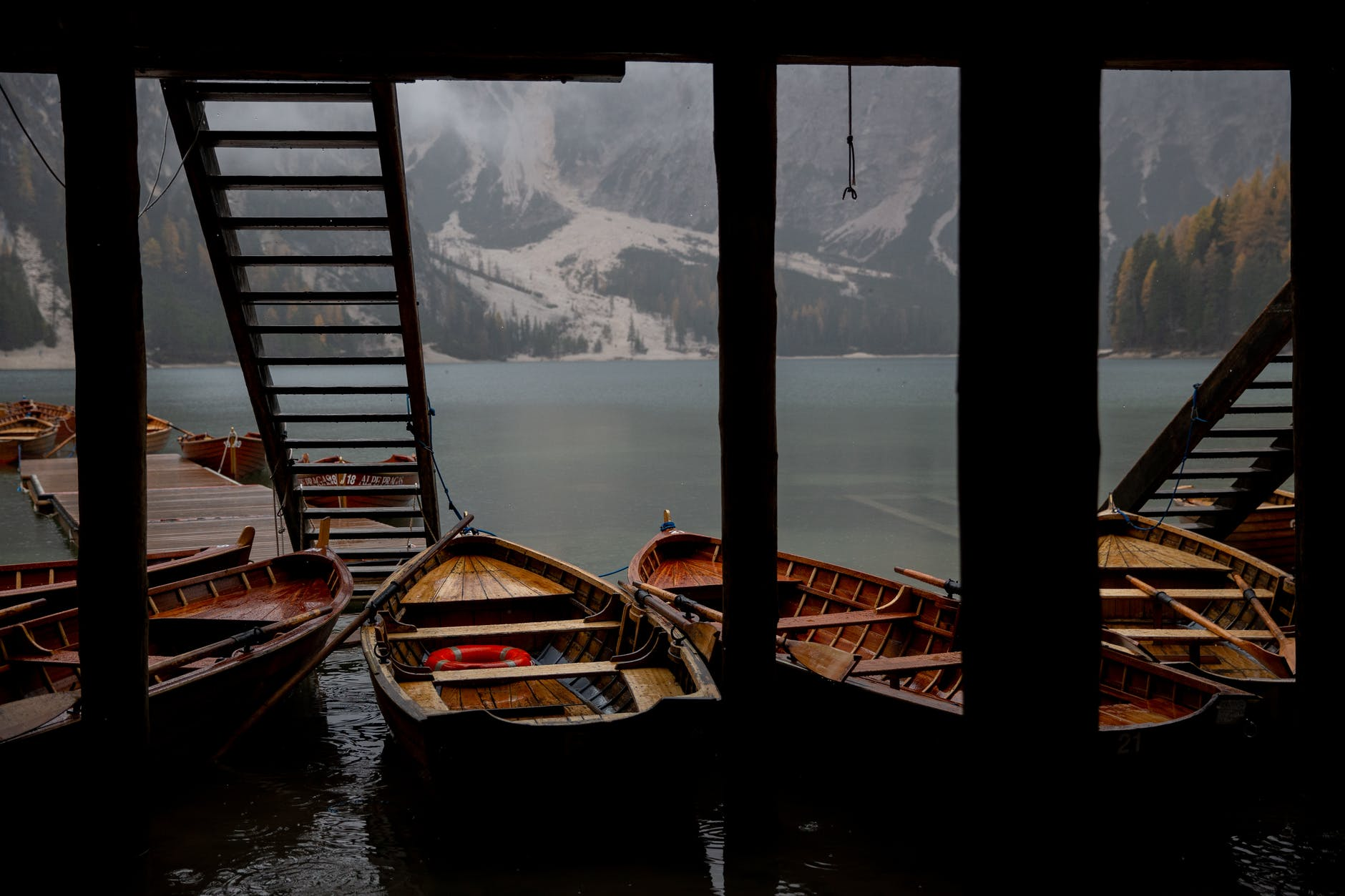 wooden boats moored under pier on lake