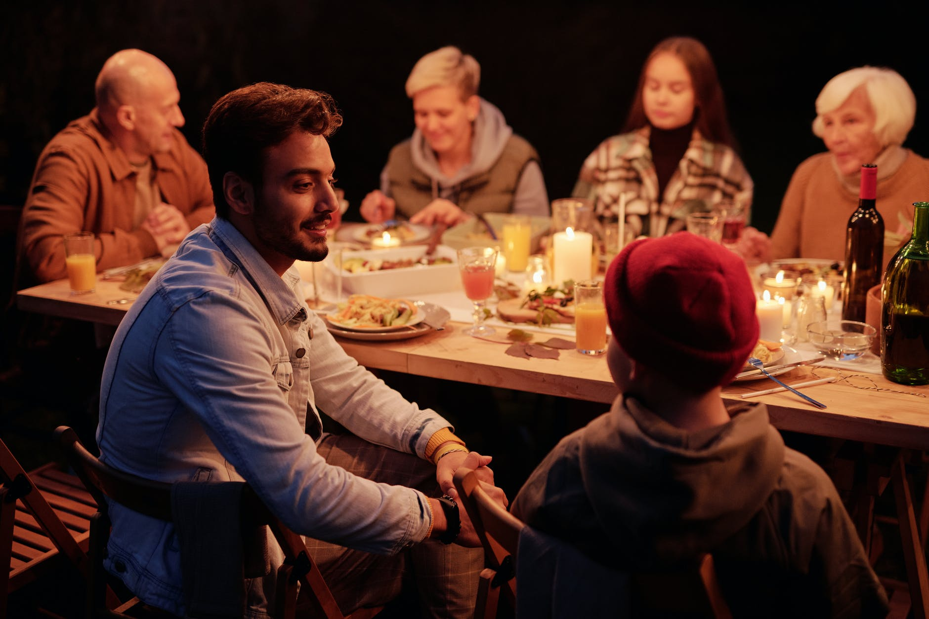 friends gathering at dinner in night garden and chatting